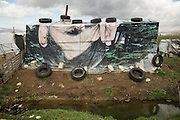Bekaa Valley, LEBANON: A discarded political billboard featuring former Iranian President Mahmoud Ahmadinejad is used as a roof on a Syrian refugee's tented shelter erected alongside an irrigation canal on agricultural land. Liam Maloney/Polaris Images