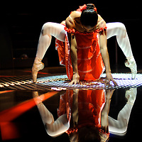 Ballerina dressed up with a Spanish style orange dress, performing on a silver surface.MR. Model relased photo.