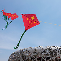 China, Beijing, String of Chinese flag paper kites fly above Olympic National Stadium on spring morning