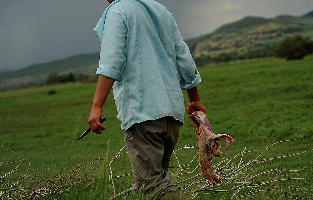 A Mongolian herder carries a leg of sheep to the cooking fire after butchering it. The herders use almost 100 percent of the animal they slaughter and eat meat at just about every meal of the day. They sustain their lives directly from the products of domesticated animals such as cattle, horses, camels, yaks, sheep, and goats, and sometimes game. — © Jeremy Lock/USAF