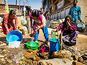 02 MARCH 2017 - SANKHU, NEPAL: Women do their laundry, while others line up for drinking water at a public tap in front of a storage depot for construction and rebuilding supplies in Sankhu. There is more construction and rebuilding going on in Sankhu, west of central Kathmandu, than in many other parts of the Kathmandu Valley nearly two years after the earthquake of 25 April 2015 that devastated Nepal. In some villages in the Kathmandu valley workers are working by hand to remove ruble and dig out destroyed buildings. About 9,000 people were killed and another 22,000 injured by the earthquake. The epicenter of the earthquake was east of the Gorka district.   PHOTO BY JACK KURTZ