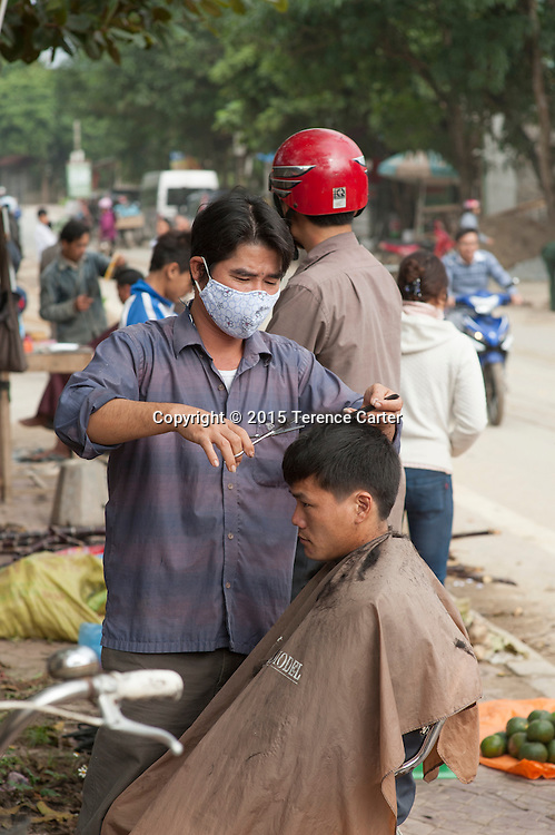 A young man gets a haircut on the streets of Sapa, Vietnam.