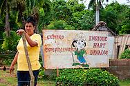 Woman and sign in Chorro de Maita, Holguin, Cuba.