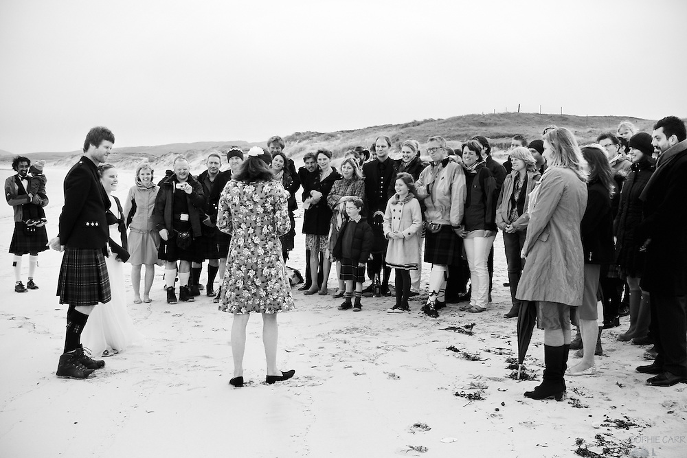 Guests watch the ceremony and vows of Jan & Carrie's wedding on Vatersay Beach