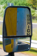 Reflection of a moving truck as seen through the passenger-side wing mirror.