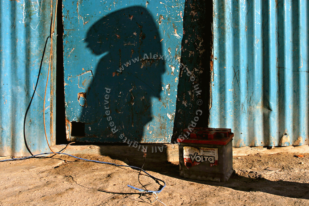 The shadow of a Bedouin girl is casted on the door of her family house in the unrecognised village of Wadi el Na'am (pop. 4000), close to Beer Sheva, the capital of the Negev, a large deserted area in the south of Israel.  Wadi el Na'am is located near a large industrial site, Ramat Hovav, has no infrastructure nor electric energy. Water is provided only via storage tanks. It has no health services as the only clinic is deemed illegal and bound to be demolished, as the rest of the structures in the area. Numbering around 200.000 in Israel, the Bedouins constitute the native ethnic group of these areas, they farm, grow wheat, olives and live in complete self sufficiency. Many of them were in these lands long before the Israeli State was created and their traditional lifestyle is now threatened by subtle Governmental policies. The seven Bedouin towns already built are all between the 10 more impoverished towns in Israel.