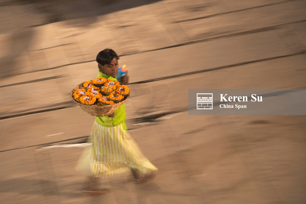 Boy carrying flower lamps on the street, Varanasi, India