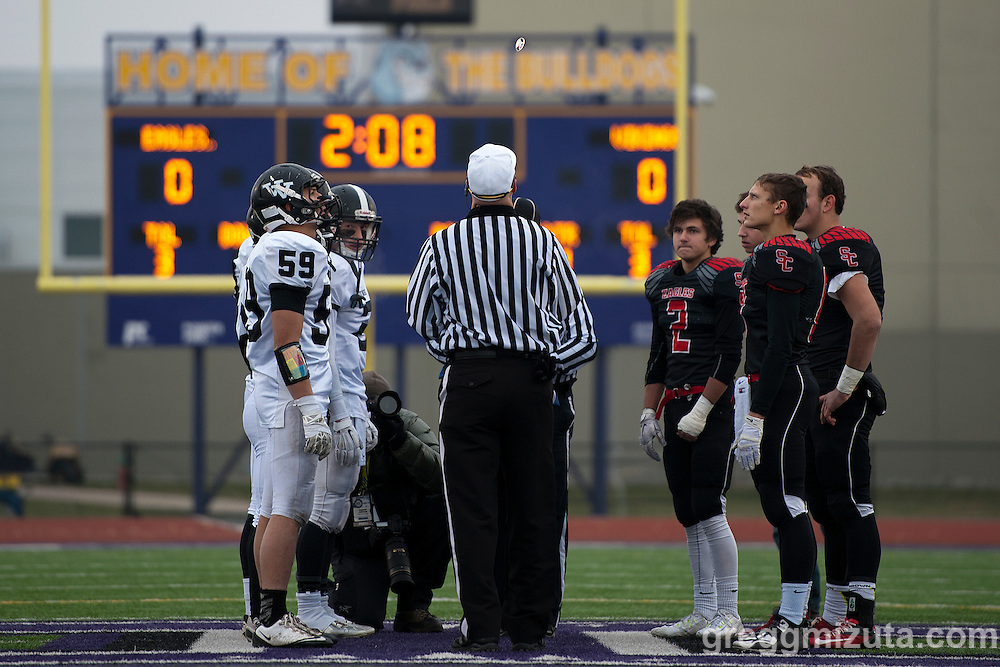 Referee Todd Gorham flips the coin as team captains for Vale (Derek Hiatt, Trace Cummings, Zac Jacobs, Garret DeVos) and Santiam Christian (Riley Roberts, Brady Patterson, Daniel Hendrix, Joshua Swigart-Risinger) watch. Santiam won the toss but deferred to the second half during the Oregon 3A Championship game at Kennison Field, Hermiston, Oregon, Saturday, November 28, 2015. Vale won 27-20.