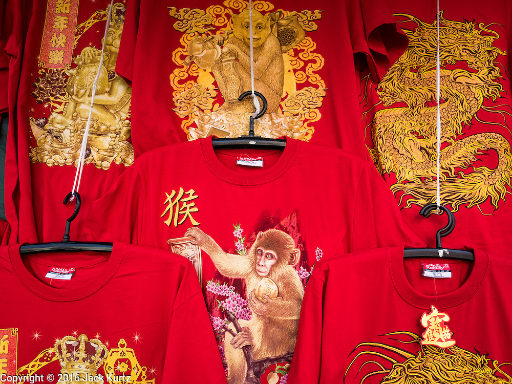 "31 JANUARY 2016 - BANGKOK, THAILAND: Chinese New Year tee shirts, decorated with monkey graphics, at a stand on Yaowarat Road in Bangkok's Chinatown. Chinese New Year, also called Lunar New Year or Tet (in Vietnamese communities) starts Monday February 8. The coming year will be the ""Year of the Monkey."" Thailand has the largest overseas Chinese population in the world; about 14 percent of Thais are of Chinese ancestry and some Chinese holidays, especially Chinese New Year, are widely celebrated in Thailand.           PHOTO BY JACK KURTZ"