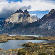 """Los Cuernos soar above Torres del Paine National Park, Chile, South America. """"The Horns"""" (about 2100 meters elevation) are a pinkish-white granodiorite intrusion formed 12 million years ago topped with an older crumbly dark sedimentary rock, exposed by freeze-thaw erosion and glaciation. Beyond a small pond (laguna) is turquoise Lake Nordenskjold. The foot of South America is known as Patagonia, a name derived from coastal giants, Patagão or Patagoni, who were reported by Magellan's 1520s voyage circumnavigating the world and were actually Tehuelche native people who averaged 25 cm (or 10 inches) taller than the Spaniards.  Published in 2008 for a Music Contact International trip brochure for Vermont Public Radio fundraising. Panorama stitched from 2 overlapping images."""