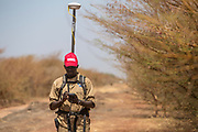 Moses Mawa is using a Differential Global Positioning System (DGPS) to accurately mark a stretch of cleared road between Pariang and Panakuach in Unity, on which UNMAS was tasked to conduct route clearance assessment. The legacy of conflict has resulted in most roads and other areas around Bentiu being contaminated with mines, such as anti-tank mines, and explosive remnants of war. Since 2013, there have been several vehicle mine accidents, which has meant some roads have been abandoned. UNMAS conducts survey and clearance for roads to ensure that civilians, humanitarians and the United Nations can safely use these roads.<br /> <br /> Photo: UNMAS/ Martine Perret