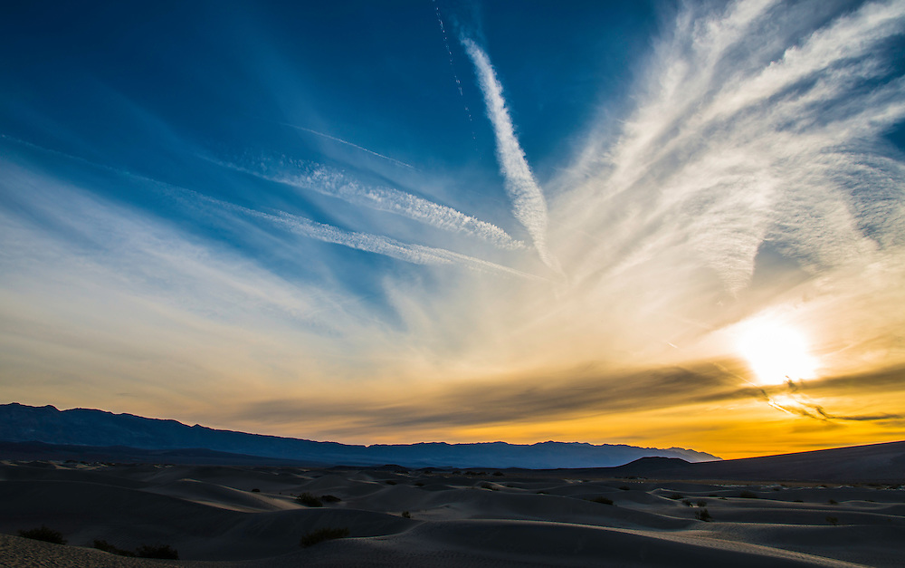 The sky above Death Valley Desert is painted with the first rays of light, a cloud formation, and a few jet contrails.