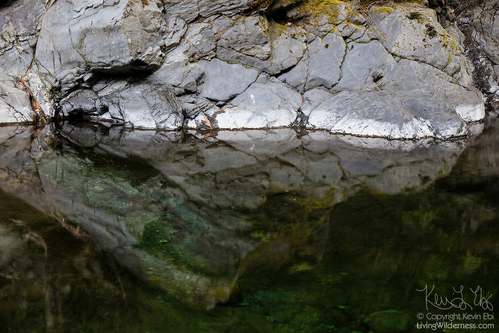 The patterns of the rock in a narrow gorge reflect on Olney Creek in the Snoqualmie National Forest near Sultan, Washington.