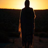 Woman watching the sun rise. Sungazing