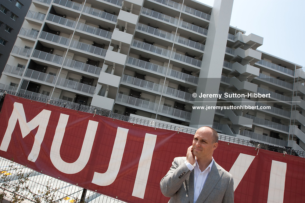Journalist Michael Booth stands outside the 'Muji Village' apartment block building in Tsudanuma, Tokyo, Japan. Monday 26th April 2010.