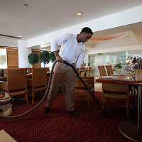 """A sudanese refugee is cleaning the restaurant  of the Royal Beach Hotel on February 28 2011. The municipality hung 1,500 red flags around the city as a sign of warning and put up hundreds of banners reading: """"Protecting our home, the residents of Eilat are drawing the line on infiltration."""" Eilat Mayor Meir Yitzhak Halevi said that 10 percent of the city's population was currently made up of migrants and that the residents feel that the city has been conquered...Photo by Olivier Fitoussi."""