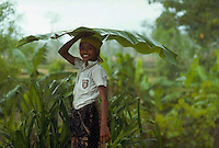 Lombok, Indonesia --- A girl carries a huge banana leaf to shelter her from a rain shower, Lombok, Indonesia. --- Image by © Owen Franken