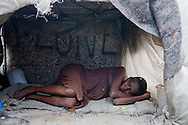 Marie Pascal Guervil lies in the small shelter on Champs de Mars where she has lived ever since the earthquake on July 14, 2010 in Port-au-Prince, Haiti.