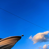 Abstract view of a boat against a blue sky  background.