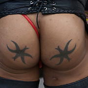 Matching buttocks tattoos of symbol star or figure at Folsom Street East S&amp;M street fair in New York City.<br />
