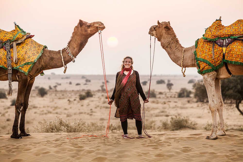 A woman posing for a picture with two camels in the Thar Desert at sunset, Rajasthan, India.