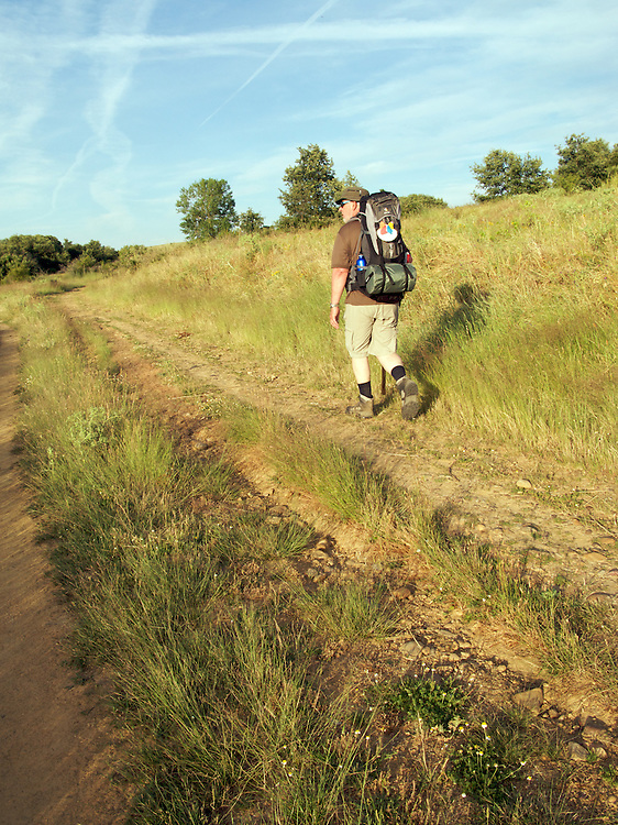 A walker leaving Santibanes de Valdeiglesias strides up into the hills. The country was typical of the area as it grew dryer along the way of Saint James heading West towards the Meseta.