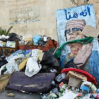 A picture of former Libyan leader Muammar Gaddafi sits beside a pile of trash in Tripoli, Libya. August 2011.
