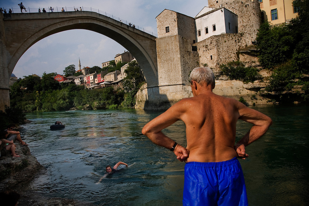 "Øyvind, a 20year old Norwegian tourist, swims ashore after his leap from the 20meter Old Bridge in Mostar...Divers and tourists at Mostar's famous Old Bridge (Stari Most) in Bosnia and Herzegovina. This bridge is the city and region's biggest tourist attraction and there are busses full of tourists coming in from Sarajevo and Dubrovnik, Croatia. For 25euros tourists can train to jump from the bridge themselves, under supervision from the ""professional"" Mostar divers known as the Mostari. .."