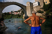 """Øyvind, a 20year old Norwegian tourist, swims ashore after his leap from the 20meter Old Bridge in Mostar...Divers and tourists at Mostar's famous Old Bridge (Stari Most) in Bosnia and Herzegovina. This bridge is the city and region's biggest tourist attraction and there are busses full of tourists coming in from Sarajevo and Dubrovnik, Croatia. For 25euros tourists can train to jump from the bridge themselves, under supervision from the """"professional"""" Mostar divers known as the Mostari. .."""