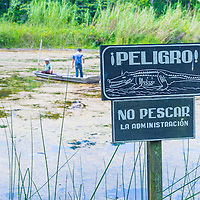 TIKAL , GUATEMALA - JULY 29 : Crocodile warning sign near an artificial pond in Tikal Guatemala's national park on July 29 2015 The pond was created by the Mayans For collecting rainwater