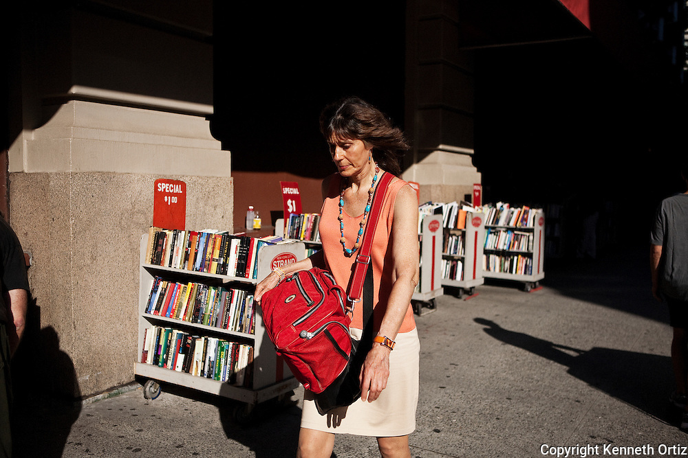 Woman Walking by the Strand Book shop on 12th Street and Broadway in downtown Manhattan.