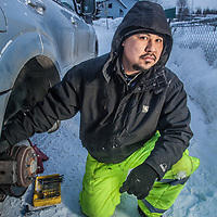 Handy man, Confessor Rivera, repairs a friend's brakes on Lois Street in the Spenard neighborhood of Anchorage