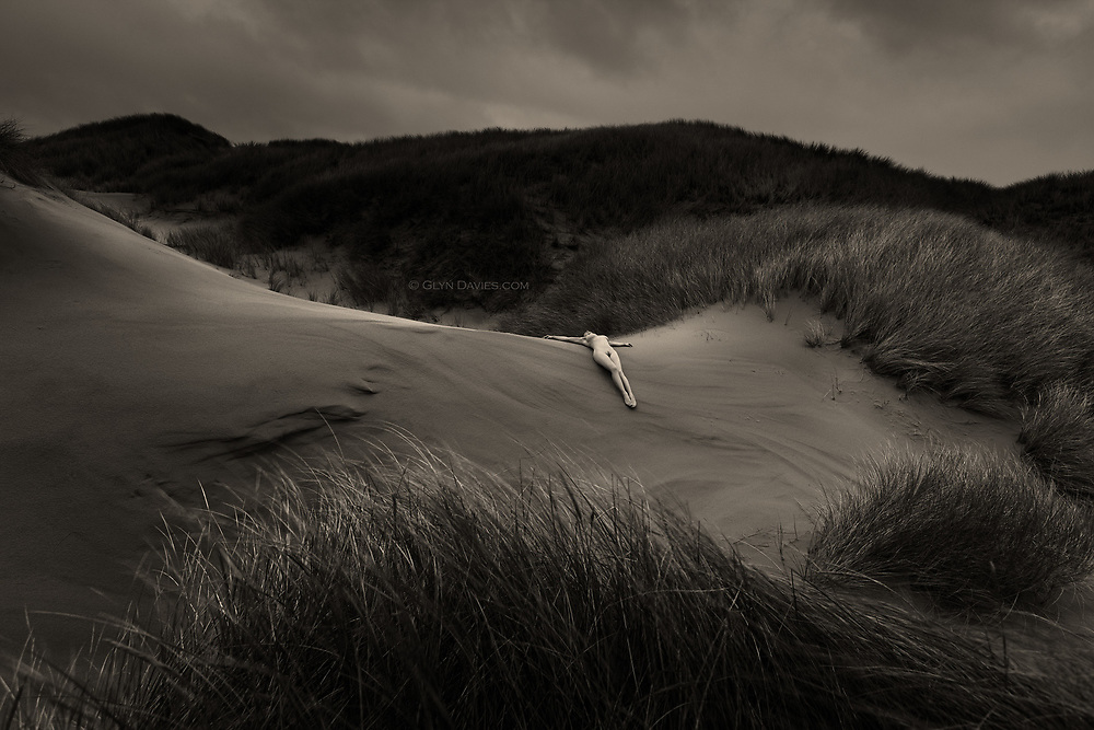 Nominated for 11th International B&amp;W Spider Awards<br /> <br /> &ldquo;The wind blew hard across the rolling landscape but the winter rain drove harder, stabbing the skin of the earth and the flesh of the figure. The sky grew dark and the hills blackened, but a gentle beam of light continued to illuminate the woman, outstretched on the dune. A firm arm of soft sand pressed into her back, supporting her and the new life now growing inside her, positioning her to face the universe&rdquo;     <br /> <br /> __________________________<br /> <br /> <br /> &ldquo;Although the nude is vital to the project and integral within the images, the images are not just &lsquo;nudes&rsquo; &ndash; they are landscapes and stories. In a way they are just simple, beautiful, dreamlike visual questions&rdquo;.