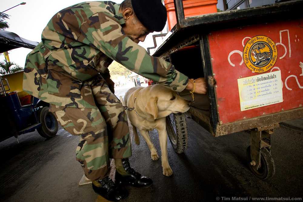 """Thai immigration and customs officials use dogs to screen people for drugs, trafficking victims, and other contraband at the Thai/Myanmar (Burma) border in Mae Sai, northern Thailand, on 15 January, 2007. A second, larger crossing is opening nearby to handle an expected increase of cross-border traffic as the """"Asian Highway"""" is built to facilitate transport in the Greater Mekong Sub-Region, from China to Thailand, Laos, Cambodia, Myanmar (Burma), and Vietnam. Historically plagued by human trafficking of the area's poorer hill tribe children, according to local NGO workers the border crossing in Mae Sai is likely to grow in importance as a transit point for trafficking victims as the new transportation infrastructure eases the movement of people from poorer countries like Laos and Myanmar (Burma)."""
