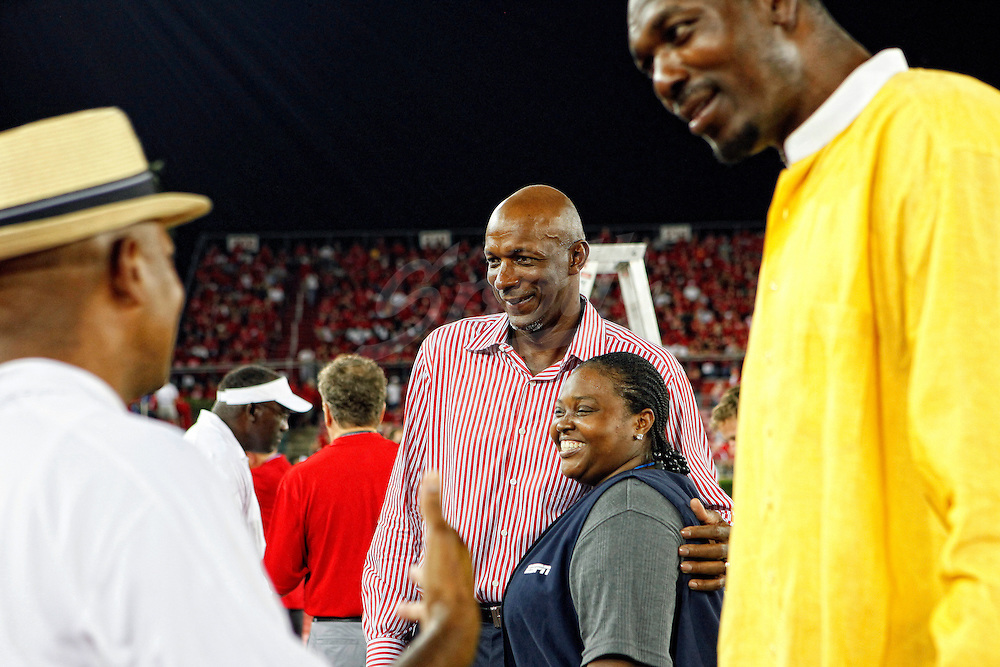 26 SEP 2009: Former Houston Cougars Clyde Drexler, rear, and Hakeem Olajuwon, right, talk with fans prior to the first half of an NCAA college football matchup between the 17th ranked University of Houston Cougars and the Texas Tech Red Raiders at Robertson Stadium in Houston, Texas. Tech leads 21 to 13 at the half. The former basketball stars participated in the coin toss.