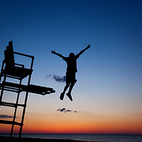 USA, Massachusetts, Barnstable, Young boy leaps from lifeguard's chair on beach along Cape Cod at sunset
