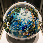 """Megaplanet, a 100-pound sphere paperweight, was made in 2006 of fused murrine, furnace-worked, applied cane drawing, applied decoration, applied gold and silver foils, by Josh Simpson (American born 1949), the culmination of 30+ years of experience. The fascinating Corning Museum of Glass (CMOG.org) covers the art, history and science of glass, brought to life through live glassmaking demonstrations, offered all day, every day, in Corning, New York, USA. The not-for-profit museum was founded in 1951 by Corning Glass Works (now Corning Incorporated) and has a collection of more than 45,000 glass objects, some over 3500 years old, the """"world's best collection of art and historical glass."""""""