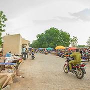 LÉGENDE: A gauche le nouveau batîment administratif du marché construit par la BAD. LIEU: Marché de Chagoua, N'Djaména, Tchad. PERSONNE(S): Un homme sur la moto (au milieu du marché). A gauche le batîment administratif du marché et à droite les vendeuses devant leurs étalages.