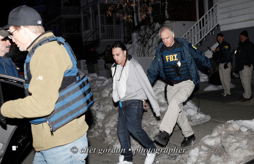 Suspected gang member Luis Tambito(center) is taken into custody from his home at 45 Bayview Terrace in the City of Newburgh, NY, on Thursday morning, February 10, 2011. Multiple law enforcement agencies, including the FBI, Orange County Sheriff's Office, NY State Police, and Newburgh Police made arrests of suspected Latin King gang members in coordinated pre-dawn raids.
