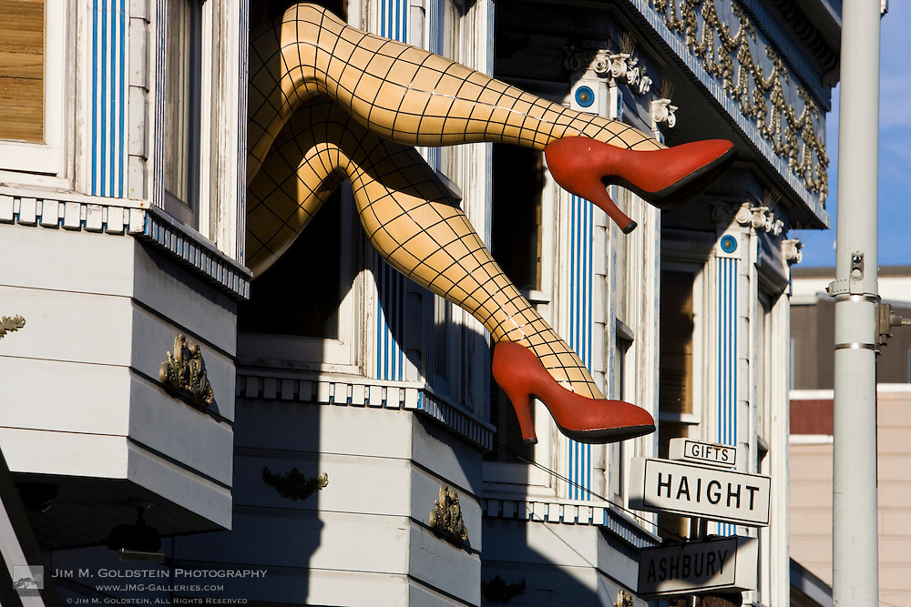 A giant pari of womans legs with fishnet stockings and red high heel shoes sticks out of a second floor window in the Haight Ashbury district of San Francisco