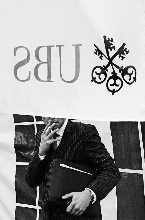 Smoker taking a break outside the annual general meeting of UBS, in which there was a shareholder revolt after catastrophic losses requiring a government bailout, following exposure to the subprime market and an investigation into tax advoidance schemes in the US, which has threatened the very concept of banking secrecy.