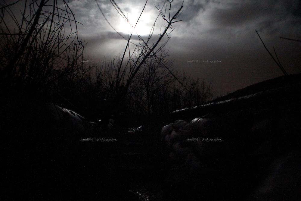 Moonlight shines through clouds on the trench at the donetsk frontline.<br /> <br /> Fascinated by war and convinced of a simple shaped nationalistic ideology, five vonuteer warriors from Europe and USA left behind their former lifes. Walking into battle in Ukraine, Ben, Alex, Craig, Charlie and Cowboy made it to the frontline and joint the right-wing militia Right Sector, supporting the ukrainian army which is short of staff. Receiving no payments but shelter, food and ammo the foreigners selfmade battlegroup Task Force Pluto is a loose union of individuals and no particular ukrainian phenomenon. The Boom Stick Brotherhood would move on to another conflict around the globe when Ukraine become boring to them. They want to be involved in battle. That&acute;s what they are aiming for. Living a dream of smoking guns, camaraderie and outdoor life. An extreme lifestyle devoted to an everyday look into the face of death.<br /> <br /> The Boom Stick Brotherhood is a multi-national, multi-religious and multi-ethnic group:<br /> Ben, an austrian infantryman travelling hot zones since years. Bored by his own reluctant national army at home he made plenty of experience in Kosovo, Syria, Iraq and Ukraine.<br /> Alex, Ben&acute;s brother in arms from austrian army times deserted and fled the country to get ultimately involed in frontline fights.<br /> Craig was fighting almost 6 years for the US-Army in Iraq and Afghanistan but got in conflict with the law afterwards. He escaped conviction by going abroad.<br /> Charlie was totally bored by his californian routine in Silicon Valley but failed to join the US-Army and French Foreign Legion. Eventually he found battle opportunities in Ukraine.<br /> Petty crook Cowboy got in trouble with US law only days before his Army unit was to deployed to Afghanistan. Later during a day release he made it from prison to France but French Foreign Legion rejected him. He gave Ukraine a go.
