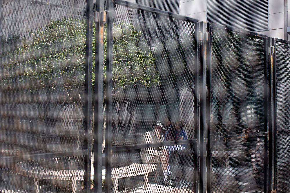 People sit in a park outside the NASCAR Hall of Fame, next to a perimeter fence for the Democratic National Convention, on Monday, September 3, 2012 in Charlotte, NC.