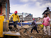 14 MARCH 2017 - BUNGAMATI, NEPAL: Workers load a dump truck with earthquake debris in Bungamati. Recovery seems to have barely begun nearly two years after the earthquake of 25 April 2015 that devastated Nepal. In some villages in the Kathmandu valley workers are working by hand to remove ruble and dig out destroyed buildings. About 9,000 people were killed and another 22,000 injured by the earthquake. The epicenter of the earthquake was east of the Gorka district.            PHOTO BY JACK KURTZ