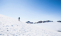 A woman wearing a backpack hiking over a snowy ridge above the clouds, Mount Rainier National Park, Washington, USA.