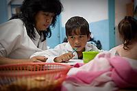 """NINIOS REALIZANDO TAREAS ESCOLARES  JUNTOS A SUS MAESTRAS DURANTE UNA CLASE DE """"APOYO ESCOLAR DULCE ESPERANZA"""", DIQUE LUJAN, PROVINCIA DE BUENOS AIRES, ARGENTINA (PHOTO © MARCO GUOLI - ALL RIGHTS RESERVED)"""