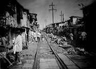 This squalid slum in Tondo is the destination of less fortunate migrants from distant provinces, Manila, Philippines.  Children must play in the refuse and mindful of trains passing through their common area...Death Throes of a Great Rainforest - Squalid destination of less fortunate migrants from distant provinces, Manila, Philippines.  Degraded land and, sometimes civil strife, drive desperate migrants to cities.  Lacking marketable urban skills or adequate education, migrants form the majority population in slums like this one in Manila.