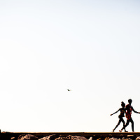 A mother and child walk along the Pass-A-Grille seawall.