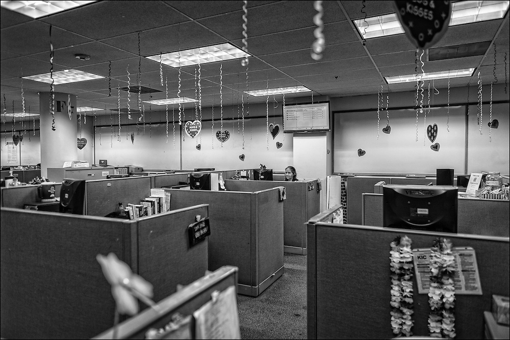 Jina Gomes, sits alone in the First Hawaiian Bank 24/7 call center located at an undisclosed unmarked location somewhere on Dillingham Blvd.