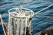 Oceanographers lowering a Niskin bottle rosette into the sea. This measuring device collects water samples from different deapth of the ocean in a sample Niskin bottle sealed by remote control. At that time measurements of Conductivity, Temperature and Depth are collected by a CTO Sensors